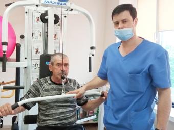 Фізтерапевт Юрій Грек проводить заняття на тренажері з пацієнтом Артуром Католиком.